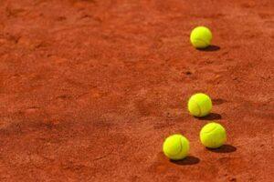 Tennis balls on clay court.