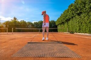 A woman sweeping clay court.